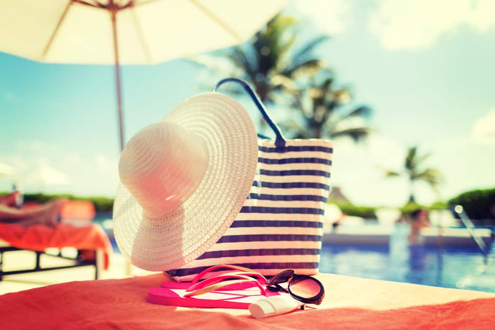 Hat, sunglasses and sunscreen on table by pool
