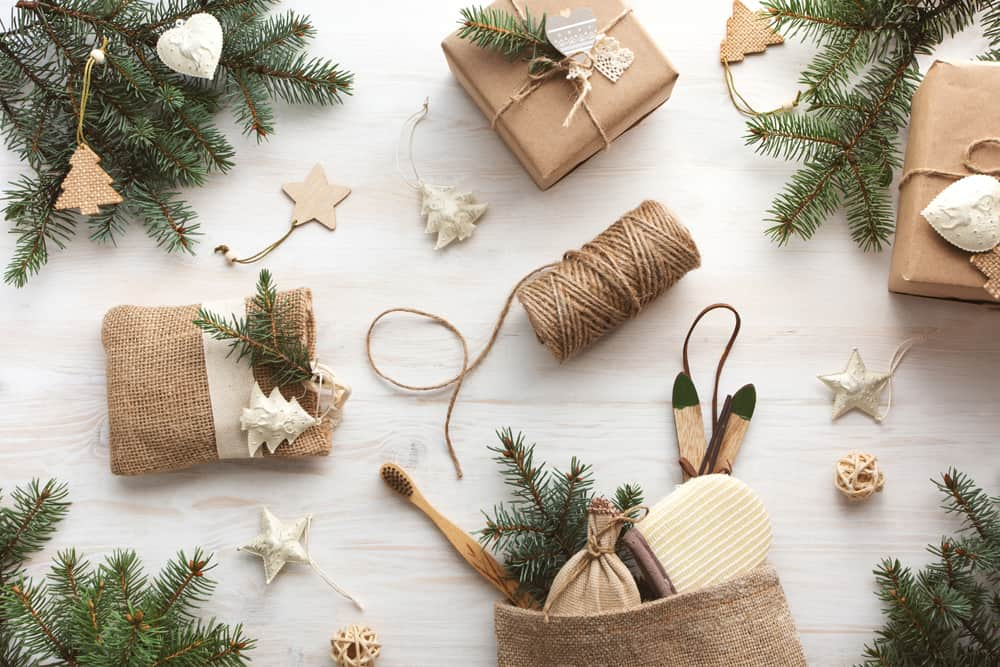 Zero waste Christmas flat lay with gifts in kraft paper and eco friendly products. Reusable sustainable recycled bath accessories in homemade burlap bag. Eco friendly new year decor with pine branches