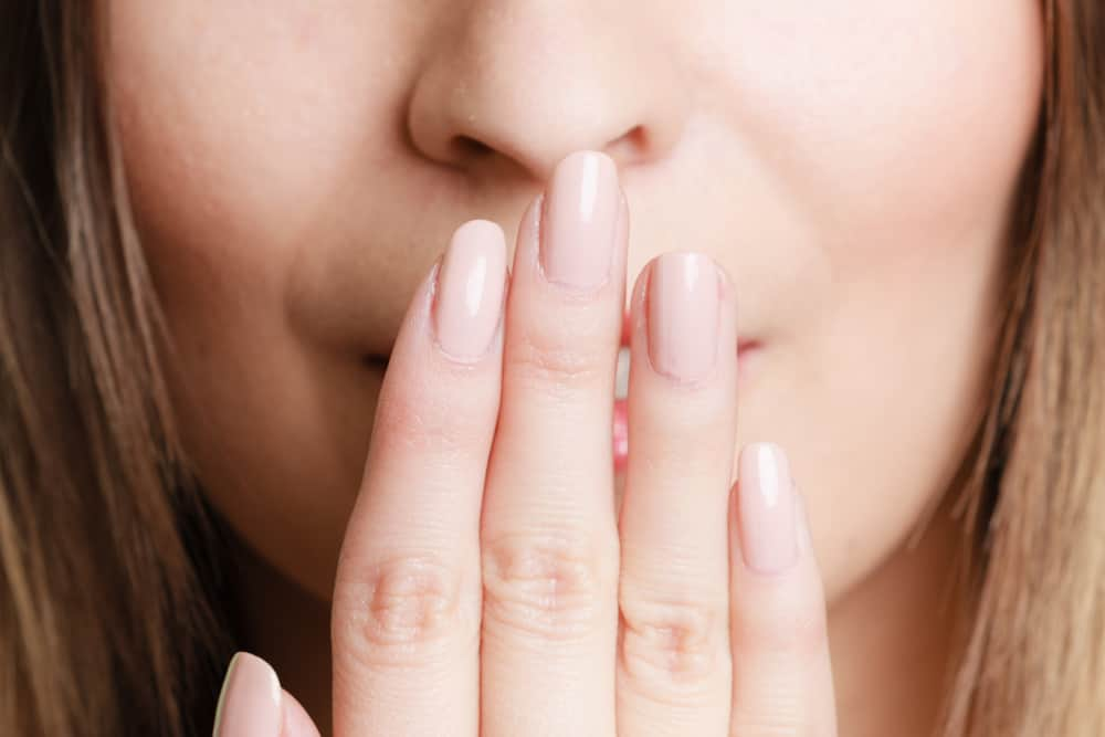 Woman's hand covering her mouth