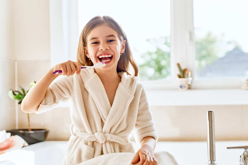 Young Girl Brushing Her Teeth in white bathrobe