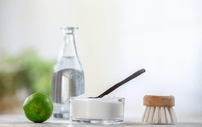 Natural cleaner. Vinegar, baking soda, salt, lemon.homemade grey wooden background