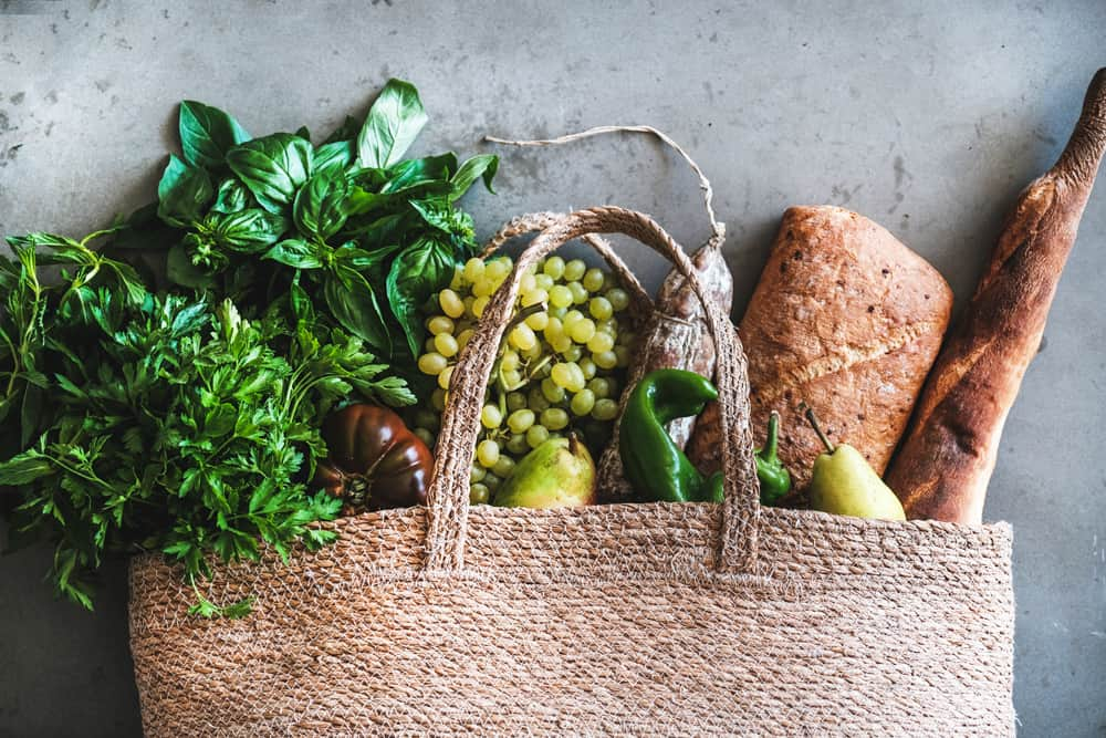 Flat-lay of healthy grocery shopping eco-friendly bag with vegetables, fruit, greens, herbs, bread and sausage over concrete background, top view. Local farmers market, shopping mall concept
