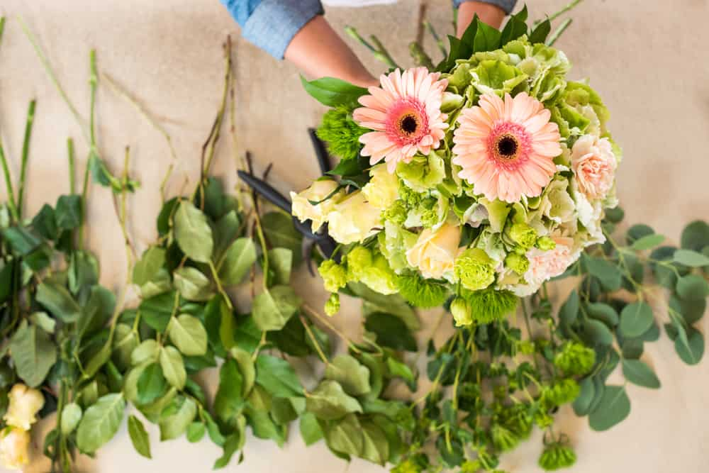 Arranging a white, green and light pink bouquet