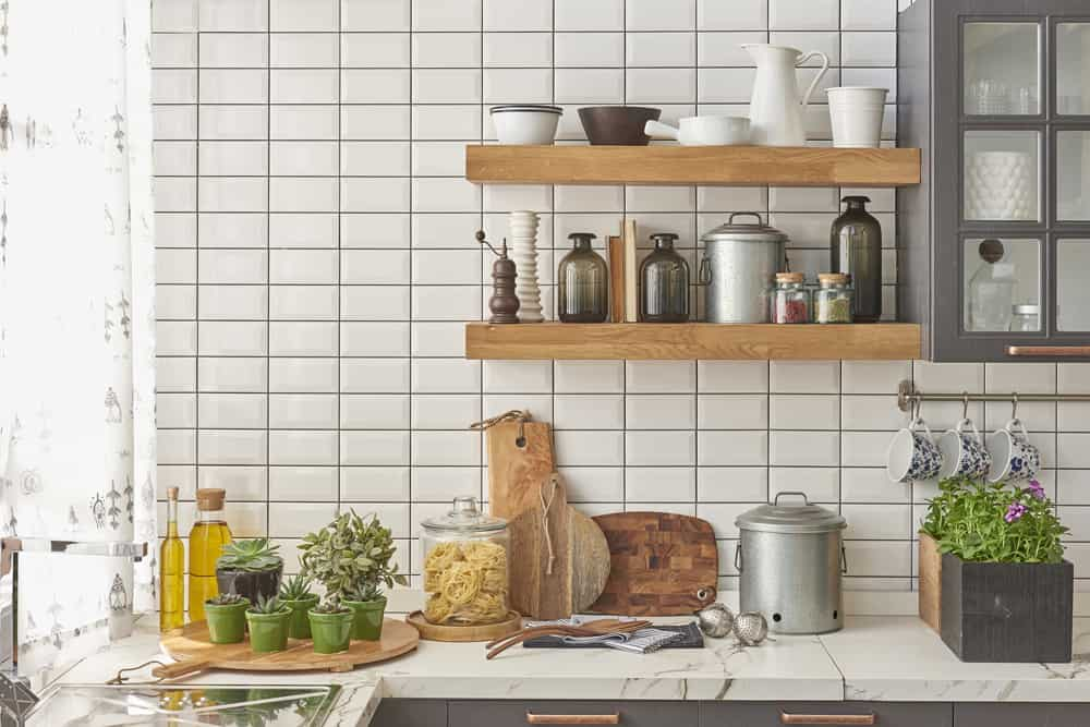 Kitchen with eco-friendly bamboo cutting boards and shelves with greenery and compost bin